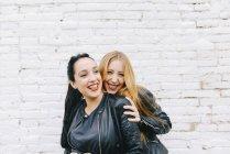 Две смеющиеся молодые женщины перед стеной из белого кирпича — стоковое фото