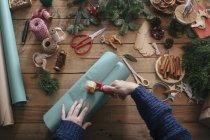Manos de mujer envolviendo regalos de Navidad - foto de stock