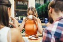 Amigos sentados ao ar livre tomando café e bolo — Fotografia de Stock