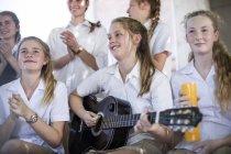Женской средней школы студент, играть на гитаре с группой друзей в школе — стоковое фото