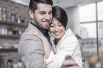 Smiling couple embracing at home — Stock Photo