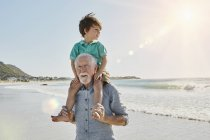 Portrait of senior man holding grandson on shoulders — Stock Photo