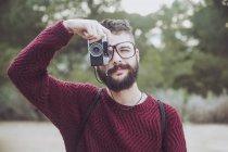 Ritratto di uomo barbuto con occhiali che scatta foto con fotocamera vintage — Foto stock
