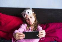 Menina deitada na cama e tomar selfie com telefone celular — Fotografia de Stock