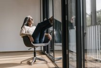 Woman with long grey hair sitting on chair at window in office — Stock Photo