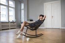 Giovane donna rilassante su sedia a dondolo a casa — Foto stock