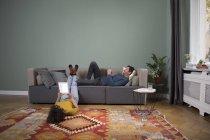 Paar entspannt zusammen im Wohnzimmer mit elektronischen Geräten — Stockfoto