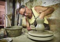Potter in workshop working on earthenware jug — Stock Photo