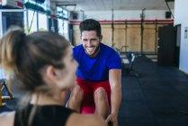 Lächelnder Mann sucht Frau im Fitness-Studio — Stockfoto