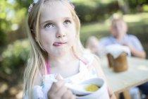Mädchen essen Gelee im Freien mit Bruder auf Hintergrund — Stockfoto