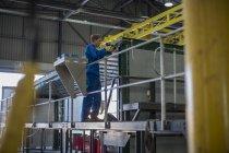 Travailleur de la construction travaillant dans un entrepôt de fabrication de camions — Photo de stock