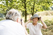 Senior man photographing woman in hat sitting in green outdoors — Stock Photo