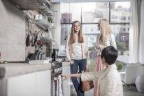 Trois amies dans une cuisine moderne avec vue sur la ville — Photo de stock