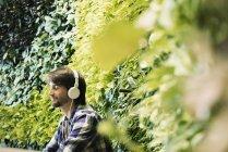 Молодой человек сидит перед зеленой стеной завода, в наушниках — стоковое фото