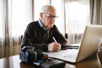 Старший фотограф, робота з його комп'ютером вдома. — стокове фото