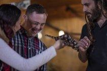 Asistente de animales mostrando serpiente de coral a hombre joven con síndrome de Down y mujer joven - foto de stock