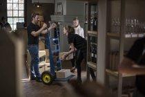Вино персонал з важкої обов'язком рука вантажівка з коробки статутного вина у винний магазин — стокове фото