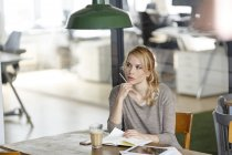 Blond woman in office with notebook thinking — Stock Photo