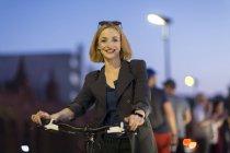 Joven mujer rubia atractiva caminando con la bicicleta al aire libre - foto de stock