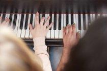 Primer plano de dos chicas tocando el piano juntas - foto de stock