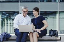 Businessman and businesswoman sitting on bench sharing laptop — Stock Photo