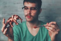 Young man painting plastic elephant figure with copper paint — Stock Photo