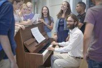 Insegnante con gruppo di studenti in piedi intorno al pianoforte — Foto stock