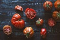 Pomodori rossi freschi interi e tagliati a metà su superficie di legno nera — Foto stock