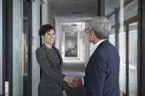 Homme d'affaires et femme d'affaires, se serrant la main — Photo de stock