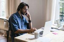 Uomo d'affari seduto in ufficio, che lavora al computer portatile e parla al telefono — Foto stock
