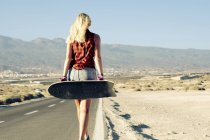 Spain, Tenerife, blond young female skater with skateboard walking on road — Stock Photo