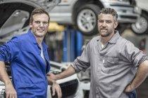 Dos mecánicos de automóviles seguros en el garaje de reparación - foto de stock