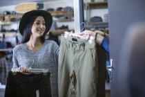 Mulher traz calças para amigo para experimentar — Fotografia de Stock