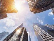 USA, New York, Manhattan, grattacieli visti dal basso, sole nel cielo sopra — Foto stock