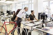 Homme d'affaires avec vélo parler à la collègue de bureau moderne — Photo de stock