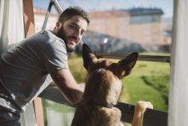 Людина і його собака дивиться крізь скло, Іспанія — стокове фото