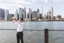 Предприниматель принимая selfie перед Манхэттен — стоковое фото