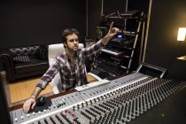 Homem trabalhando na sala de controle de um estúdio de gravação levantando a mão — Fotografia de Stock