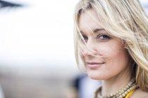 Портрет улыбающейся блондинки, смотрящей в камеру — стоковое фото