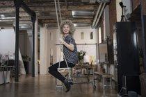 Портрет усміхається жінка, сидячи на гойдалки в сучасні офісні — стокове фото