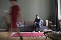 Uomo seduto sul divano in soggiorno mentre la donna passa in primo piano — Foto stock