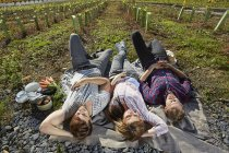 Relaxed friends lying on blanket in countryside — Stock Photo