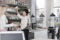 Two female friends in modern kitchen with city view — Stock Photo