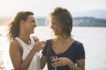 Italien, Gardasee, zwei glückliche junge Frauen am Seeufer mit Glas Wein — Stockfoto