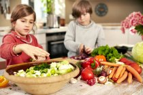 Garçon et fille, hacher les légumes dans la cuisine — Photo de stock