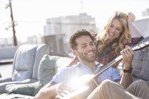 Homem tocando guitarra com mulher jovem no telhado — Fotografia de Stock