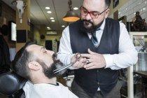 Barba da barbiere tagliente uomo nel salone del barbiere — Foto stock
