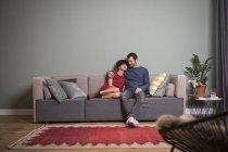 Paar sitzt zusammen auf der Couch in moderner Wohnung — Stockfoto