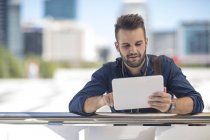 Cape Town, South Africa,Casual male seated outside with digital tablet — Stock Photo
