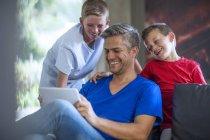 Crianças com pai olhar para tablet digital, riso — Fotografia de Stock